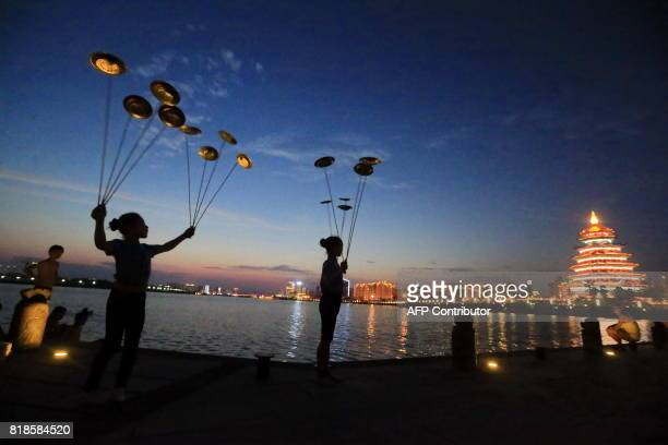 TOPSHOT Members of the Sichuan Province Acrobatic Troupe practice outdoors in the evening to avoid the summer heat in Suining in China's southwest...