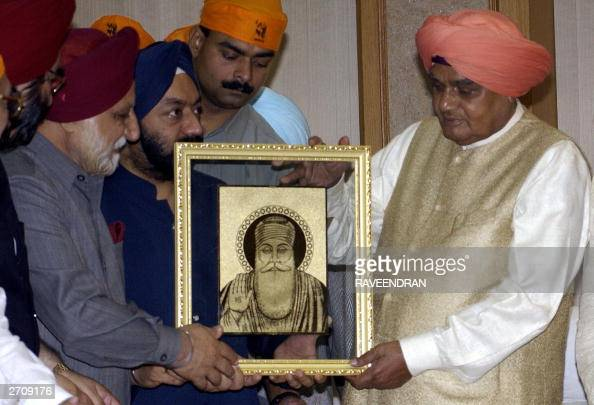 Members of the Sikh community present a portrait of Sikh Guru Nanak to Indian Prime Minister Atal Behari Vajpayee during a prayer meeting at his...