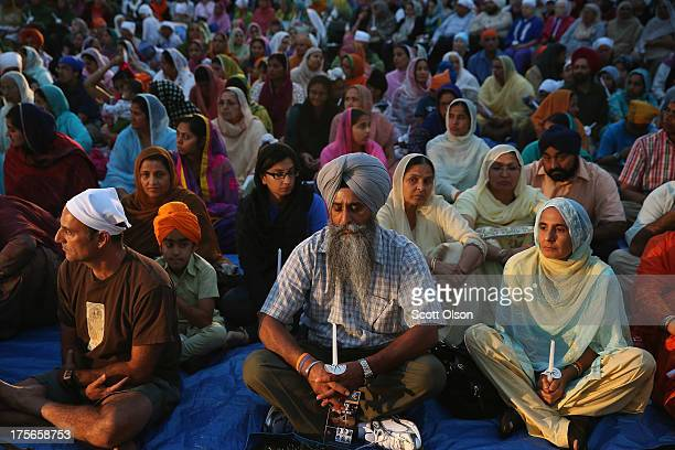 Members of the Sikh Temple of Wisconsin their guests and supporters attend a vigil to mark the oneyear anniversary of the shooting at the temple...