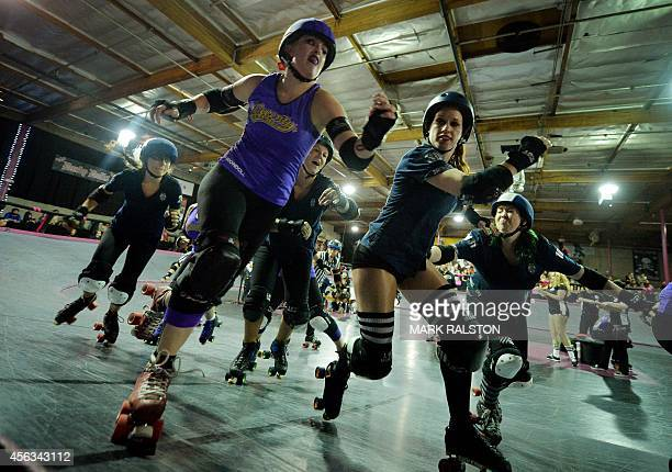 Members of the Sirens team compete against the Varsity Brawlers during the LA Derby Dolls women's banked track roller derby event in Los Angeles on...