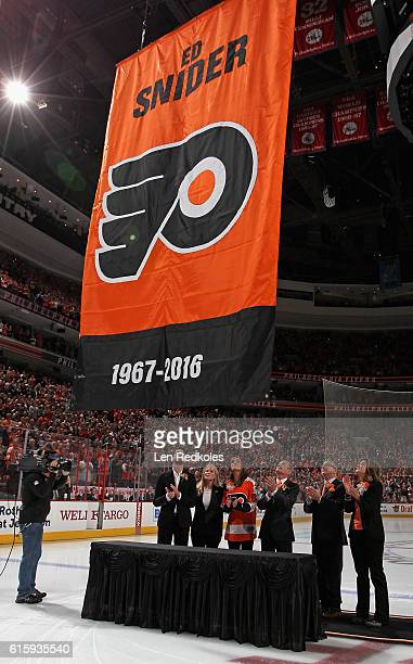 Members of the Snider family watch as a banner is unfurled during a pregame ceremony honoring the late Ed Snider former chairman of Comcast Spectacor...
