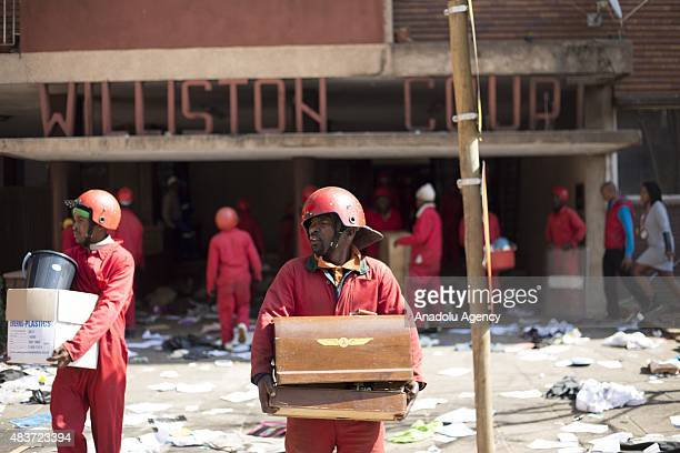 Members of the so called 'Red Ants' private security company carry household items belonging to residents of the Williston Building onto the street...