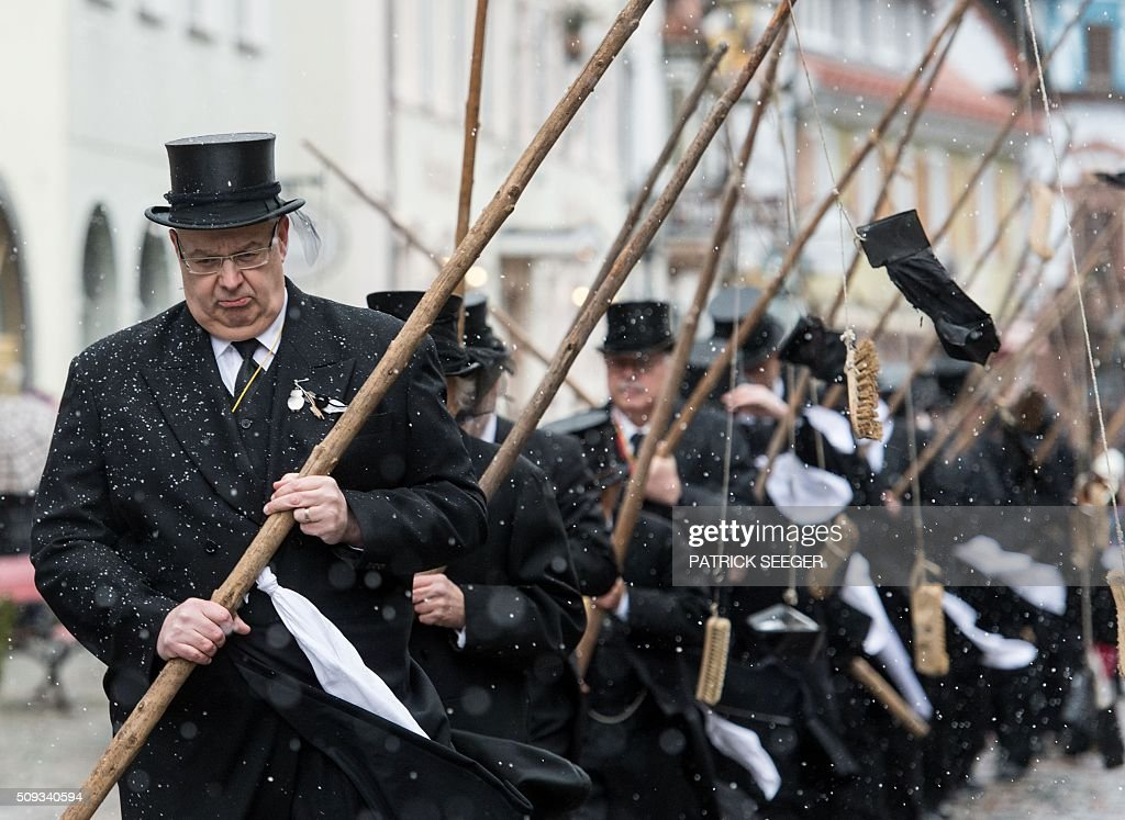 Members of the so-called 'Geldwaeschergilde' (money launderer guild) perform a funeral procession as they mourn over the end of the carnival season on Ash Wednesday, February 10, 2016 in Wolfach, southern Germany. In many cities and villages of southwestern Germany, carnival enthousiasts traditionally carry their wallets they have emptied during the days from Fat Thursday to Ash Wednesday to a fountain or river to wash them there and hang them up for drying. / AFP / dpa / Patrick Seeger / Germany OUT