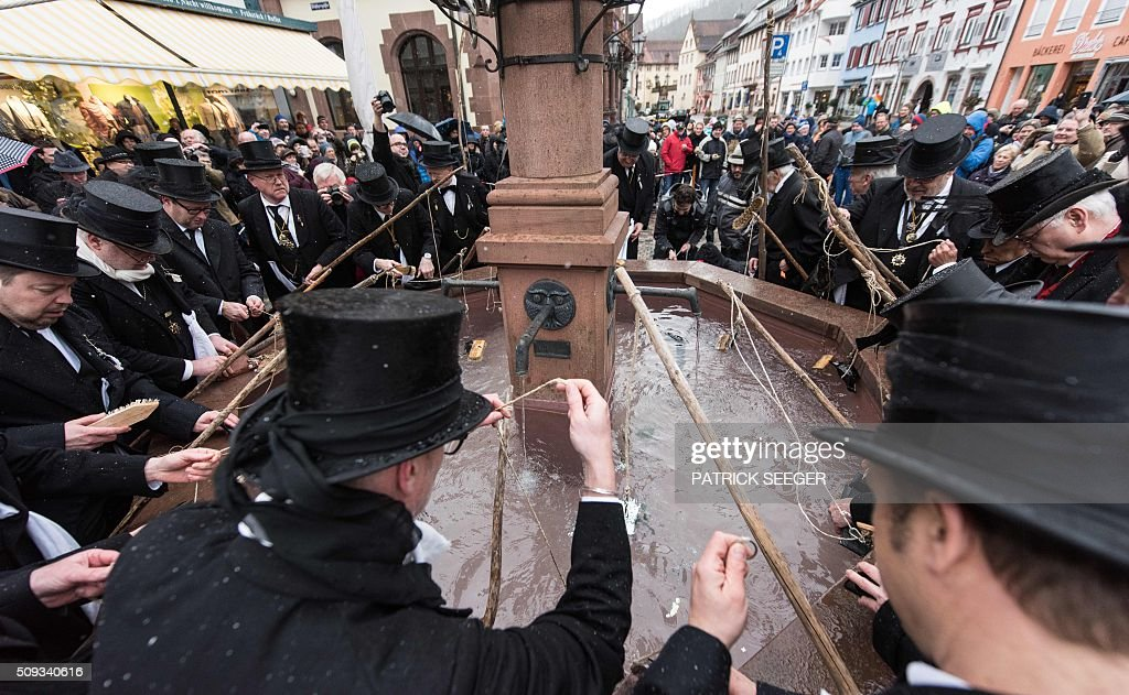 Members of the so-called 'Geldwaeschergilde' (money launderer guild) wash their wallets in a fountain as they mourn over the end of the carnival season on Ash Wednesday, February 10, 2016 in Wolfach, southern Germany. In many cities and villages of southwestern Germany, carnival enthousiasts traditionally carry their wallets they have emptied during the days from Fat Thursday to Ash Wednesday to a fountain or river to wash them there and hang them up for drying. / AFP / dpa / Patrick Seeger / Germany OUT