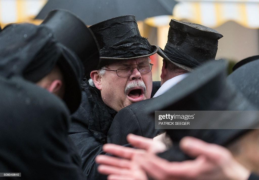 Members of the so-called 'Geldwaeschergilde' (money launderer guild) weep over the end of the carnival season on Ash Wednesday, February 10, 2016 in Wolfach, southern Germany. In many cities and villages of southwestern Germany, carnival enthousiasts traditionally carry their wallets they have emptied during the days from Fat Thursday to Ash Wednesday to a fountain or river to wash them there and hang them up for drying. / AFP / dpa / Patrick Seeger / Germany OUT