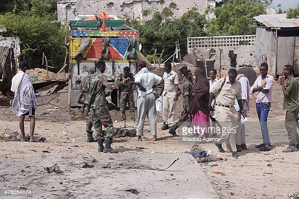 Members of the Somalian security forces inspect the dead bodies at the scene after a car bombing attack on United Arab Emirates embassy convoy killed...