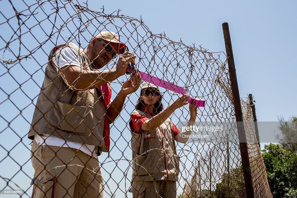 Members of the Sousse Red Crescent place a ribbon on the fence at the front of the Imperial Marhaba hotel on June 26, 2016 in Sousse, Tunisia. Today marks the one year anniversary of the Sousse Beach terrorist attack, which killed 38 people including 30 Britons. Before the 2011 revolution, tourism in Tunisia accounted for approximately 7% of the country's GDP. The two 2015 terrorist attacks at the Bardo Museum and Sousse Beach saw tourism numbers plummet even further forcing hotels to close and many tourism and hospitality workers to lose their jobs.