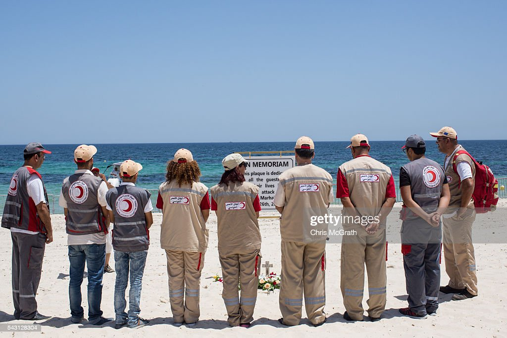 Members of the Sousse Red Crescent take a moment of silence for the victims of the Sousse Beach attack at a memorial placed on the beach in front of the Imperial Marhaba hotel on June 26, 2016 in Sousse, Tunisia. Today marks the one year anniversary of the Sousse Beach terrorist attack, which killed 38 people including 30 Britons. Before the 2011 revolution, tourism in Tunisia accounted for approximately 7% of the country's GDP. The two 2015 terrorist attacks at the Bardo Museum and Sousse Beach saw tourism numbers plummet even further forcing hotels to close and many tourism and hospitality workers to lose their jobs.