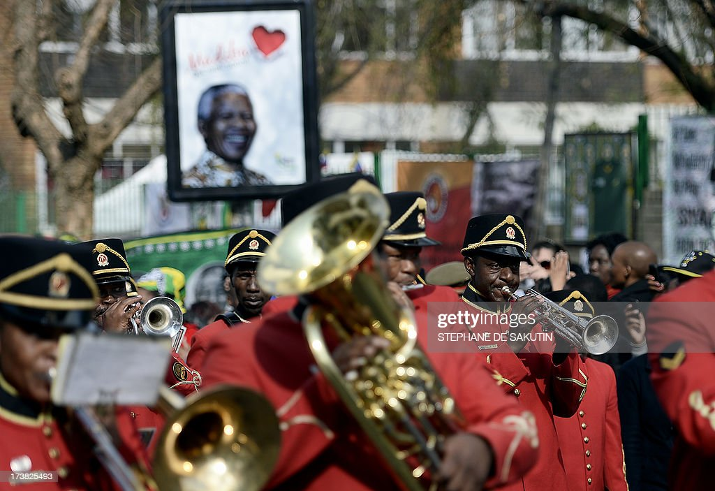 Members of the South African Army band parade to wish a happy birthday to former South African President Nelson Mandela on July 18, 2013 outside the Medi Clinic Heart Hospital in Pretoria. Mandela's health is 'steadily improving', South Africa's presidency said on July 18 as the anti-apartheid legend began spending his 95th birthday in hospital. Children in schools around the country kicked off the celebrations by singing 'Happy Birthday' to Mandela, on a day that also marked the 15th anniversary of his marriage to third wife Graca Machel.The United Nations declared the Nobel Peace laureate's birthday Mandela Day in 2010, but for many this year it takes on extra poignancy.