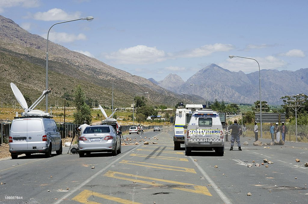 Members of the South African Police Services and media wait on the N1 Highway, which is still closed after two days of violent clashes between police and striking farmworkers(not visible), on January 11, 2013 in de Doorns, a small farming town about 140Km North of Cape Town, South Africa. The farm workers have said that they they will not return to work on the fruit growing region's farms until they receive a daily wage of at least R150($17) per day, which is about double what they currently earn.