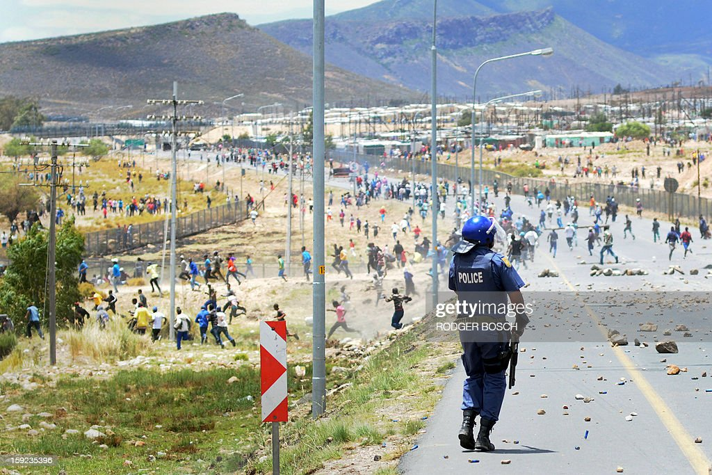 Members of the South African Police Services clash with striking farmworkers during violent clashes, on January 10, 2013 in de Doorns, a small farming town about 140Km North of Cape Town, South Africa. The farm workers have said that they they will not return to work on the fruit growing region's farms until they receive a daily wage of at least R150($17) per day, which is about double what they currently earn.