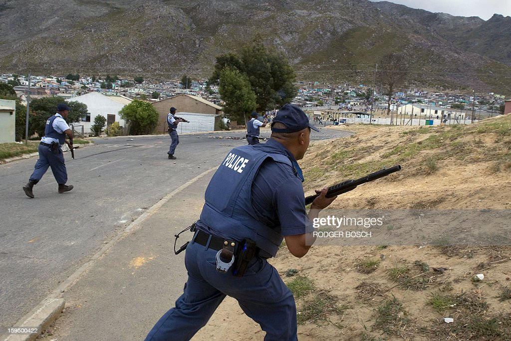 Members of the South African Police Services duck rocks thrown by protestors during an illegal strike by farmworkers, on January 14, 2012 in Villiersdorp, a small farming town about 100Km North of Cape Town, South Africa. The farm workers have said that they they will not return to work on the fruit growing region's farms until they receive a daily wage of at least R150($17) per day. BOSCH