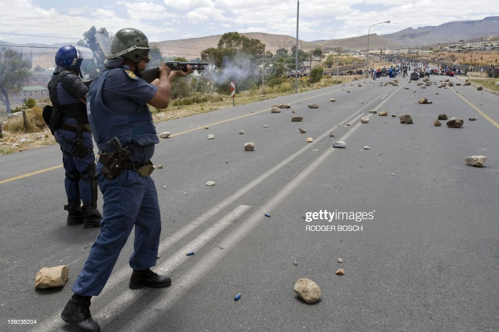 Members of the South African Police Services fire rubber bullets at striking farmworkers during violent clashes, on January 10, 2013 in De Doorns, a small farming town about 140Km North of Cape Town, South Africa. The farm workers have said that they they will not return to work on the fruit growing region's farms until they receive a daily wage of at least R150($17) per day, which is about double what they currently earn. One of the men wears a red t-shirt of the ruling African National Congress(ANC).