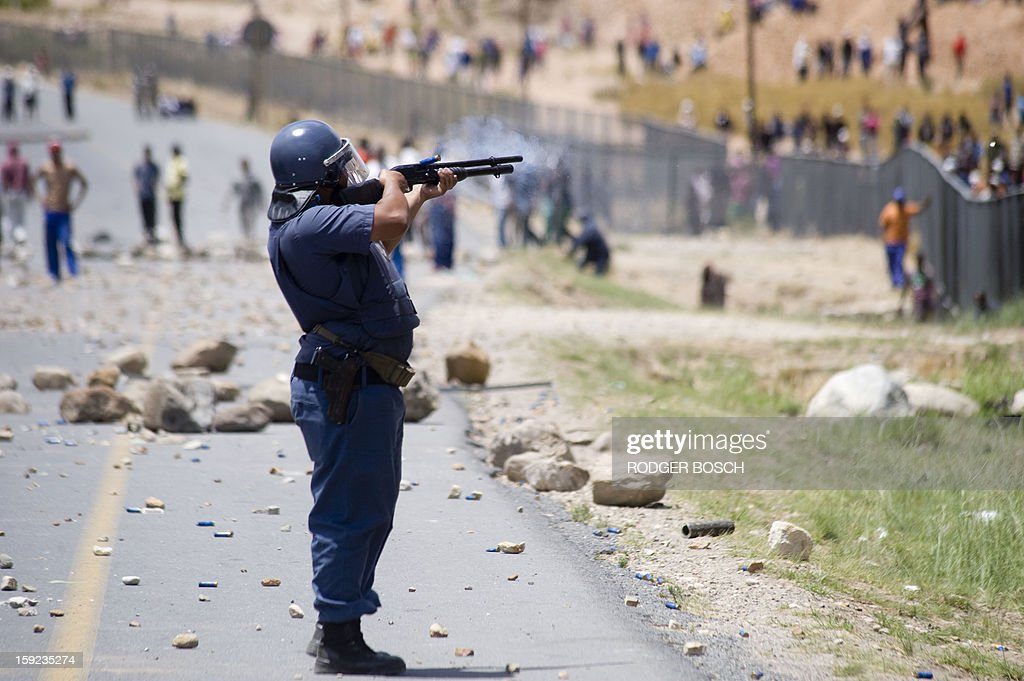 Members of the South African Police Services fire rubber bullets at striking farmworkers and other protestors during violent clashes, on January 10, 2013 in de Doorns, a small farming town about 140Km North of Cape Town. The farm workers have said that they they will not return to work on the fruit growing region's farms until they receive a daily wage of at least R150($17) per day, which is about double what they currently earn.