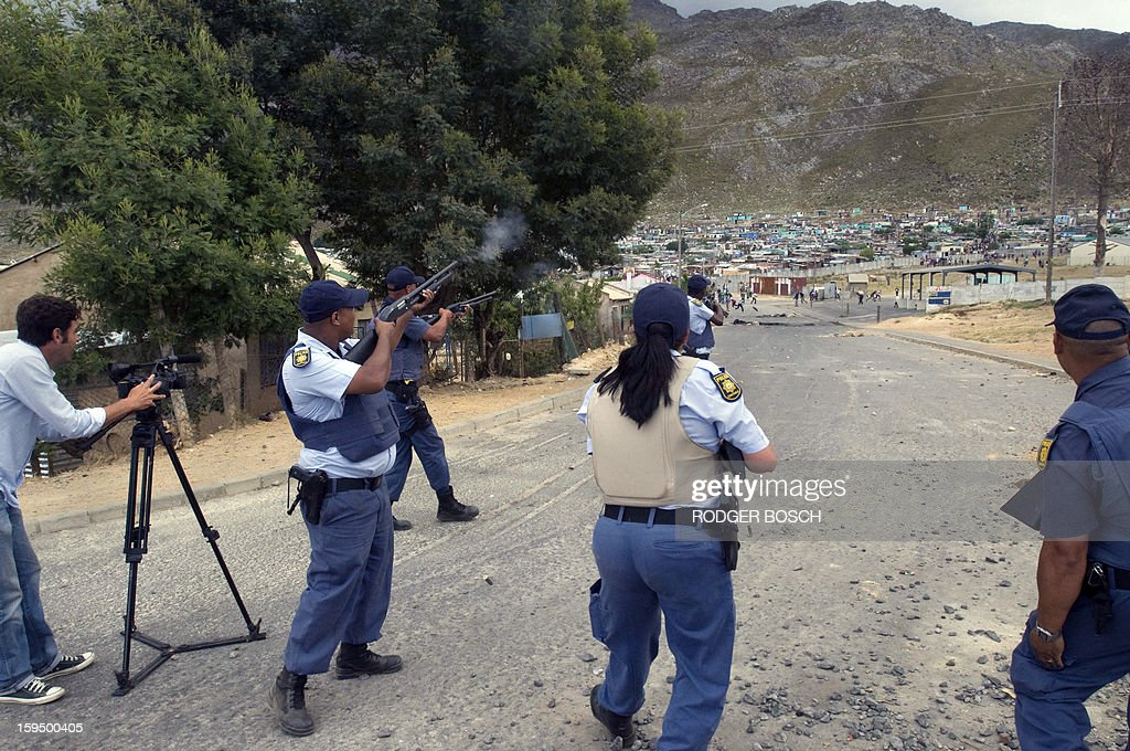 Members of the South African Police Services fire rubber bullets at rock-throwing protestors during an illegal strike by farmworkers, on January 14, 2012 in Villiersdorp, a small farming town about 100Km North of Cape Town, South Africa. The farm workers have said that they they will not return to work on the fruit growing region's farms until they receive a daily wage of at least R150($17) per day. BOSCH