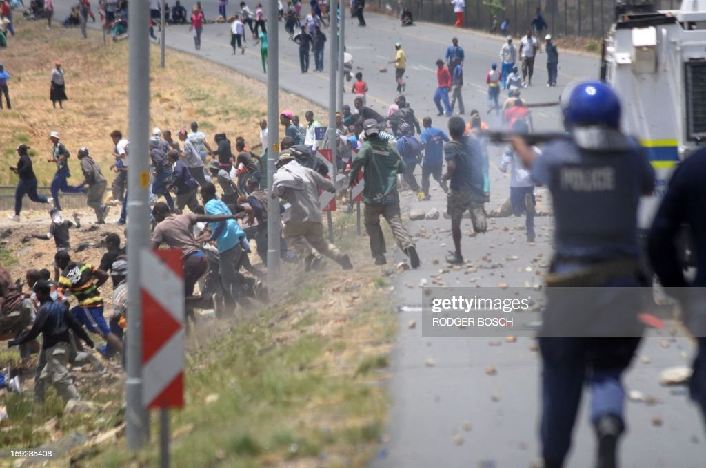 Members of the South African Police Services fire rubber bullets striking farmworkers during violent clashes, on January 10, 2013 in de Doorns, a small farming town about 140Km North of Cape Town, South Africa. The farm workers have said that they they will not return to work on the fruit growing region's farms until they receive a daily wage of at least R150($17) per day, which is about double what they currently earn. . AFP PHOTO / RODGER BOSCH