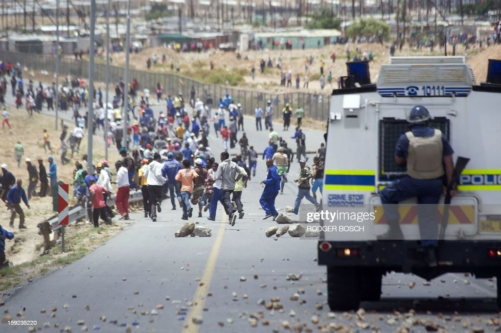Members of the South African Police Services in an armoured vehicle move towards a group of striking farmworkers during violent clashes, on January 10, 2013 in de Doorns, a small farming town about 140Km North of Cape Town, South Africa. The farm workers have said that they they will not return to work on the fruit growing region's farms until they receive a daily wage of at least R150($17) per day, which is about double what they currently earn.