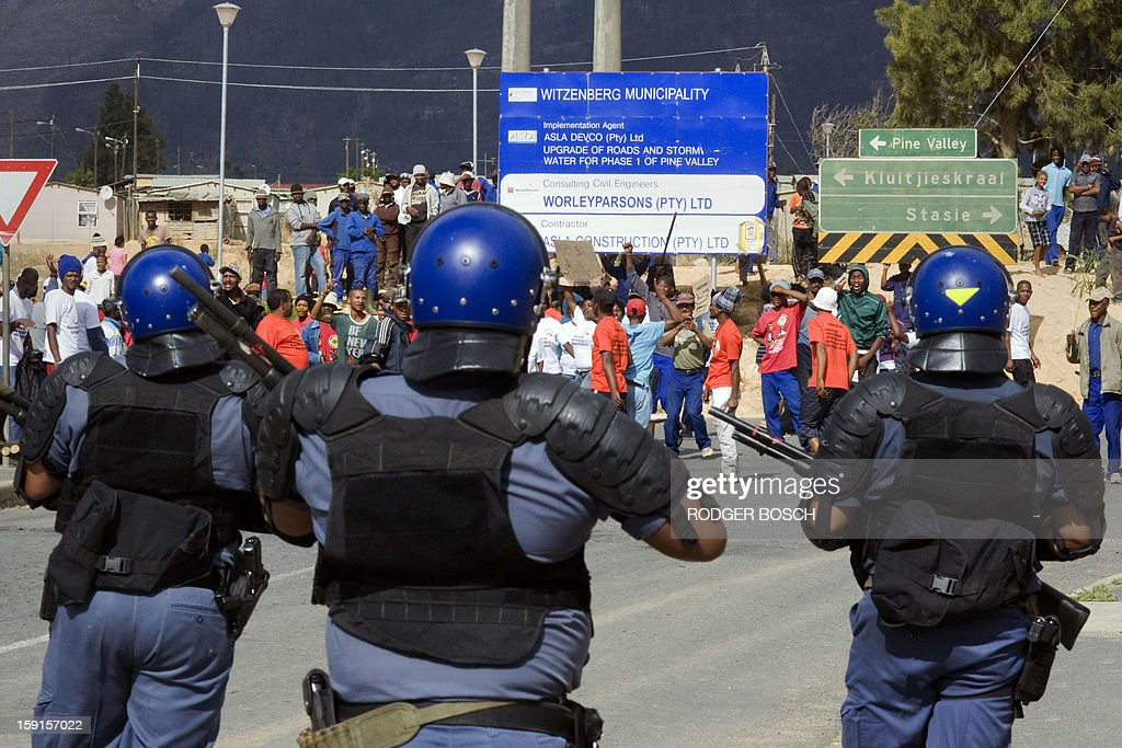 Members of the South African Police Services monitor striking farmworkers on January 9, 2013 in Wolseley, a small rural town about 120Km North of Cape Town. Workers have said they will not return to the fruit growing region's farms until they receive a daily wage of at least $17 (13 euros) per day. AFP / RODGER