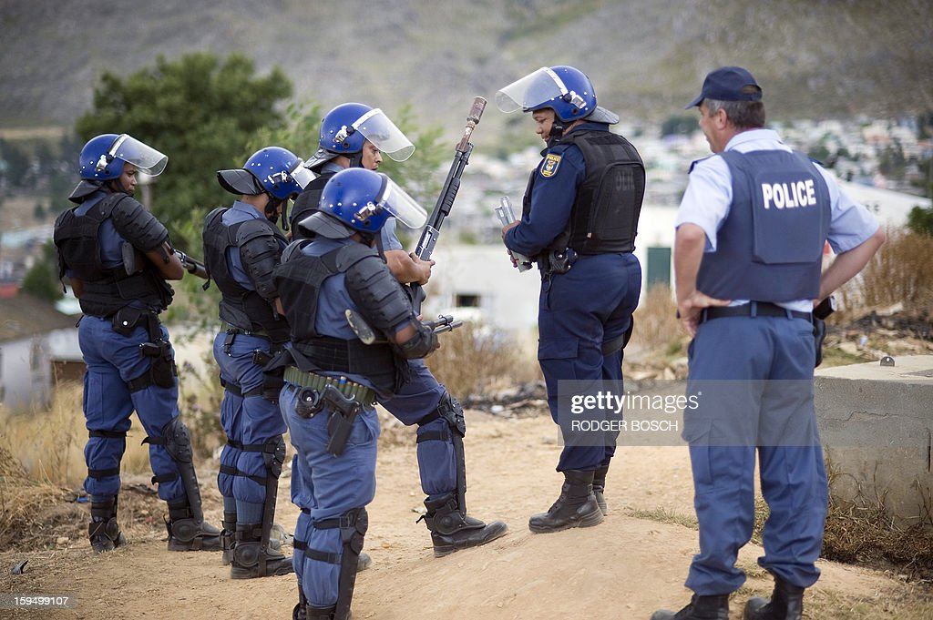Members of the South African Police Services reload their shotguns, some with tear-gas grenades during an illegal strike by farmworkers, on January 14, 2012 in Villiersdorp, a small farming town about 100Km North of Cape Town, South Africa. The farm workers have said that they they will not return to work on the fruit growing region's farms until they receive a daily wage of at least R150($17) per day. BOSCH