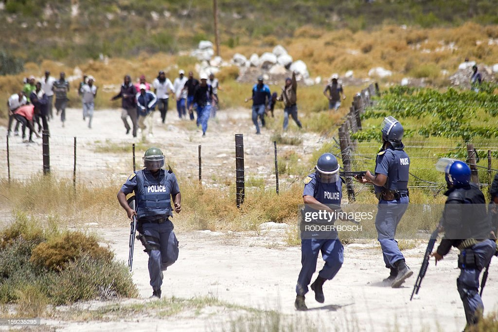 Members of the South African Police Services retreat from a group of rock-throwing striking farmworkers during violent clashes, on January 10, 2013 in de Doorns, a small farming town about 140Km North of Cape Town, South Africa. The farm workers have said that they they will not return to work on the fruit growing region's farms until they receive a daily wage of at least R150($17) per day, which is about double what they currently earn.