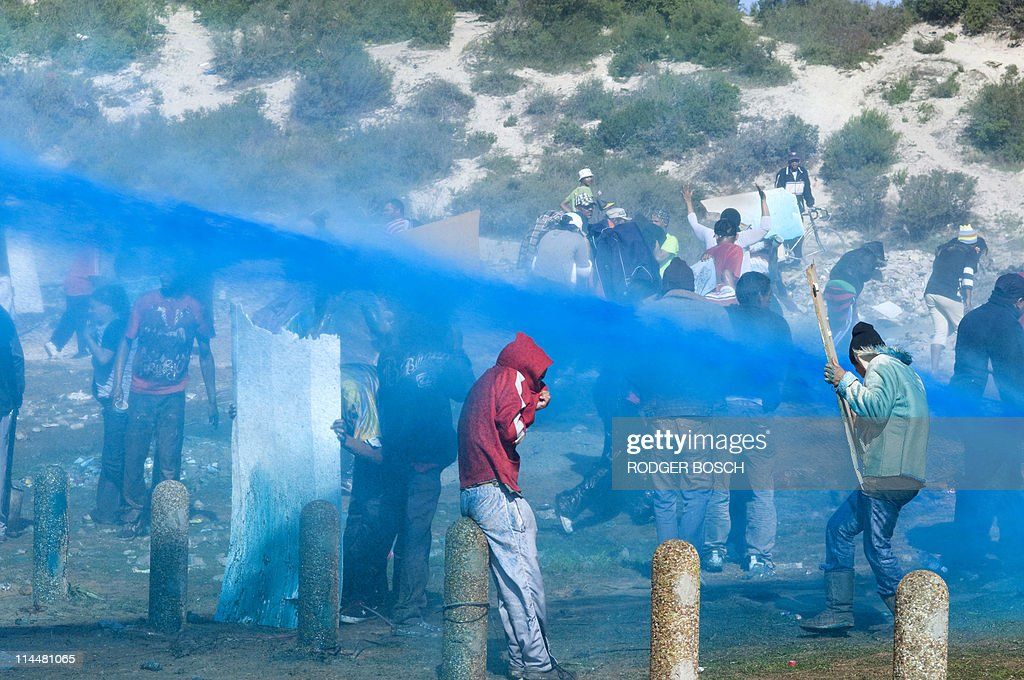 Members of the South African Police Services (not visible) spray a mixture of blue dye, water, and tear gas at squatters on May 17, 2011 in Tafelsig, Mitchells Plain, some 30Kms from the centre of Cape Town, South Africa. Groups of people living in backyard shacks in the area decided to build shacks on an open piece of land. This confrontation happened the day before the South African Local Government Elections, where housing and access to land are seen as critical issues.