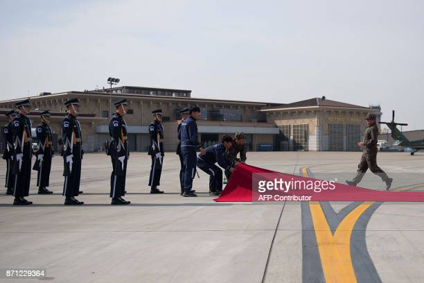 Members of the South Korean honor guard line up as the red carpet is positioned in front of Air Force One as US President Donald Trump arrives in...