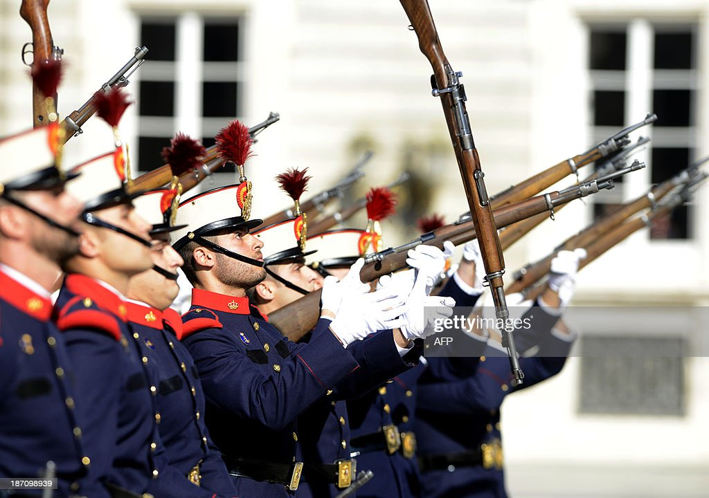 Members of the Spanish Royal Guard flip their weapons during the monthly changing of the guard ceremony at the royal palace in Madrid on November 6, 2013.