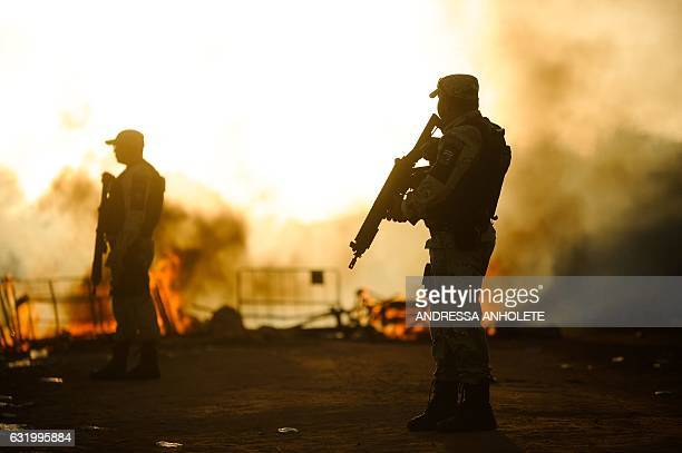 TOPSHOT Members of the special police battalion stand near makeshift barricades on fire in protest for the transfer of some 200 prisoners from the...