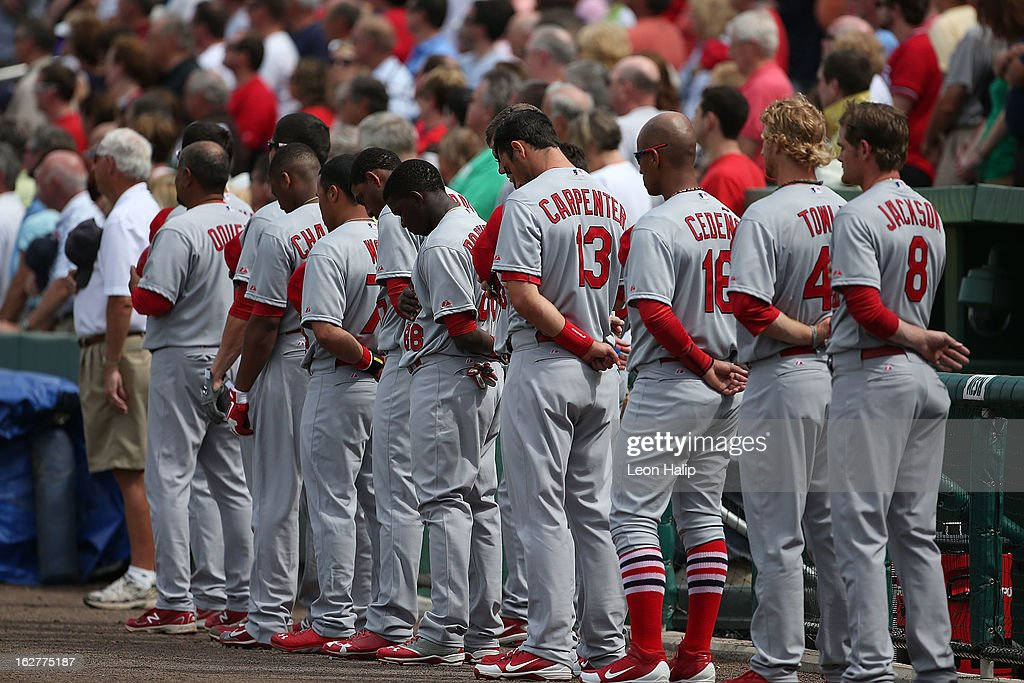 Members of the St. Louis Cardinals stand for a moment of silence for Stan Musial prior to the start of the game against the Boston Red Sox at JetBlue Park on February 26, 2013 in Fort Myers, Florida.
