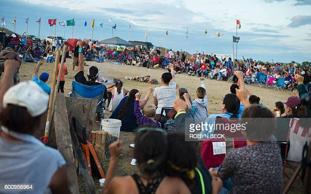 Members of the Standing Rock Sioux tribe and their supporters gather in a circle in the center of camp to hear speakers and singers at a protest...