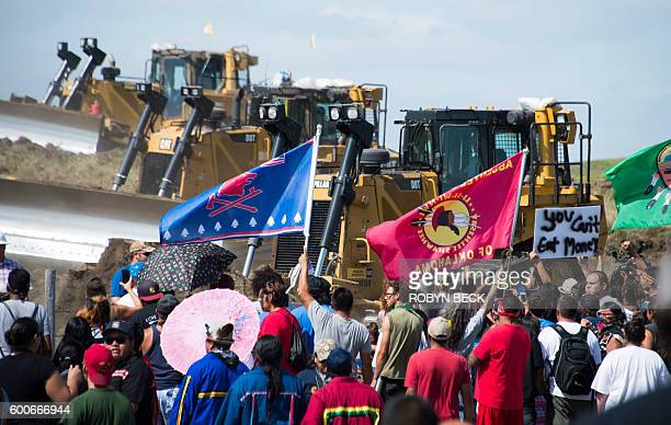 Members of the Standing Rock Sioux Tribe and their supporters opposed to the Dakota Access Pipeline confront bulldozers working on the new oil...