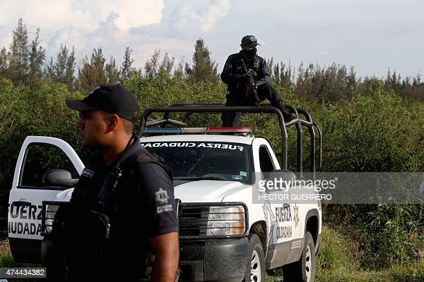 Members of the State police stand guard at the entrance of the ranch where gunmen took cover during an intense gun battle with the police along the...