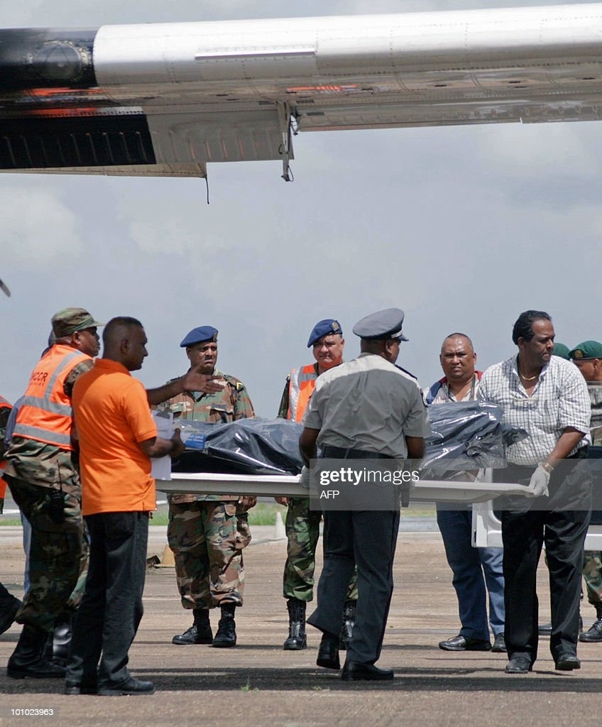 Members of the Surinam National Coordination Center for Disaster Management (NCCR) download the remains of the victims of the crashed plane, upon arrival at the Zorg en Hoop airport in Paramaribo on May 17, 2010. Eight people, including pilot and co-pilot, died in a plane crash on May 15 in the hinterlands of Suriname. This is the third accident, second with casualties, with an Antonov airplane of Blue Wing airline in two years in Surinam. AFP PHOTO/Louis ALFAISIE