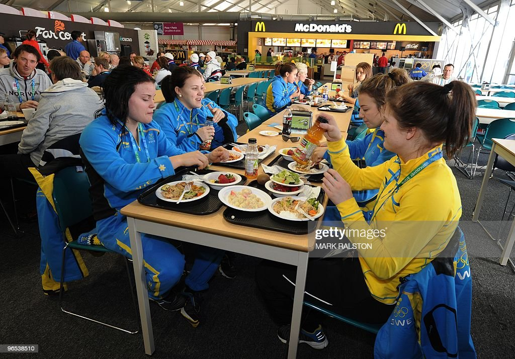 Members of the Swedish Woman's Hockey team eat in the Winter Olympic athletes dining hall at the Olympic Village in downtown Vancouver on February 9...