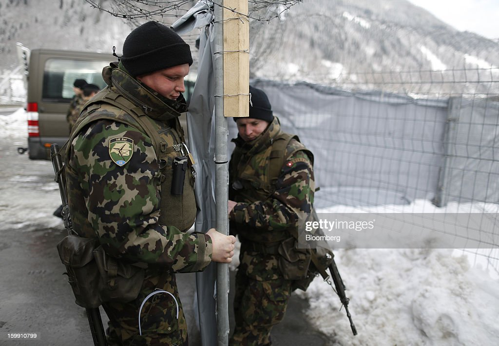 Members of the Swiss army move a security barrier into position near to the Congress Center, the venue for the World Economic Forum (WEF) in Davos, Switzerland, on Tuesday, Jan. 22, 2013. As policy makers and executives debate the latest remedies to draw a line under Europe's worst crisis since World War II, Swiss officers are now using the World Economic Forum as a testing ground for plans to turn the entire country into a fortress. Photographer: Simon Dawson/Bloomberg via Getty Images