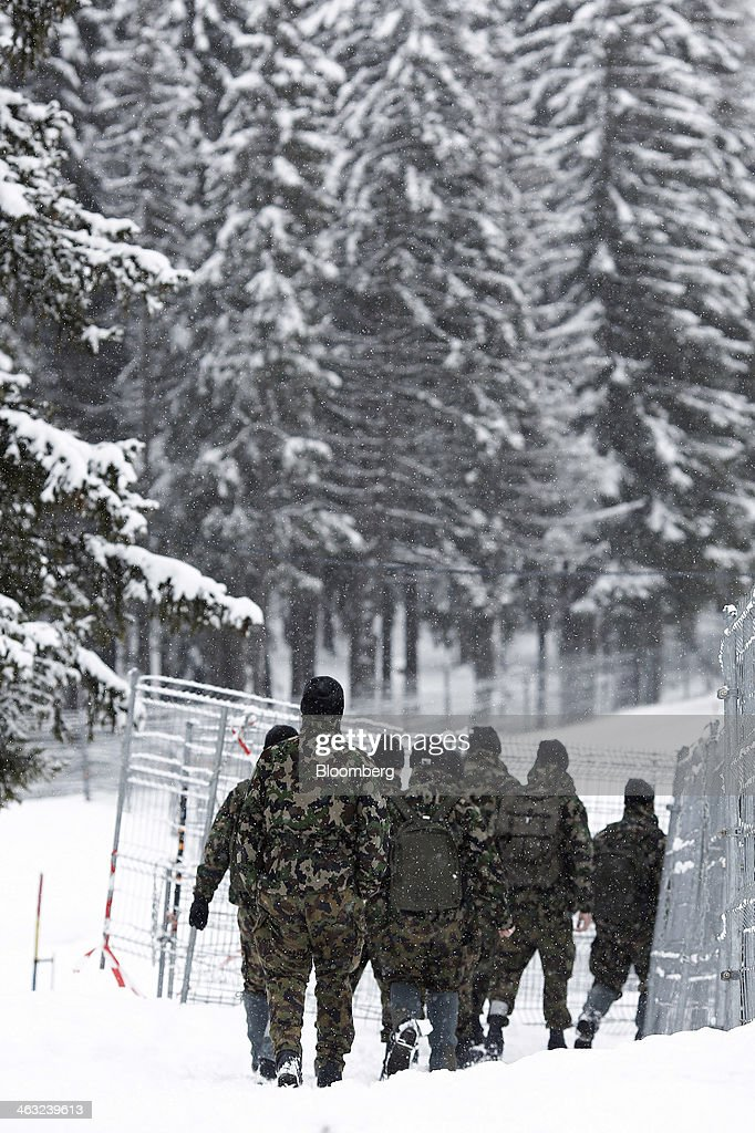 Members of the Swiss army walk around the perimeter metal security fence near to the Kongress Zentrum, or Congress Center, the venue for the World Economic Forum (WEF) in Davos, Switzerland, on Friday, Jan. 17, 2014. Next week the business elite will gather in the Swiss Alps for the 44th annual meeting of the World Economic Forum (WEF) in Davos for the five day event which runs from Jan. 22-25. Photographer: Simon Dawson/Bloomberg via Getty Images