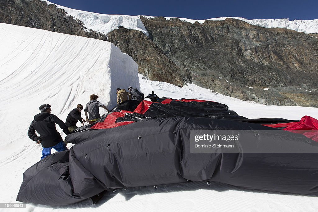 Members of the Swiss Freeski Team after the training are folding the Air2Bag which is used to learn new tricks in the halfpipe on September 13, 2013 in Saas-Fee, Switzerland.