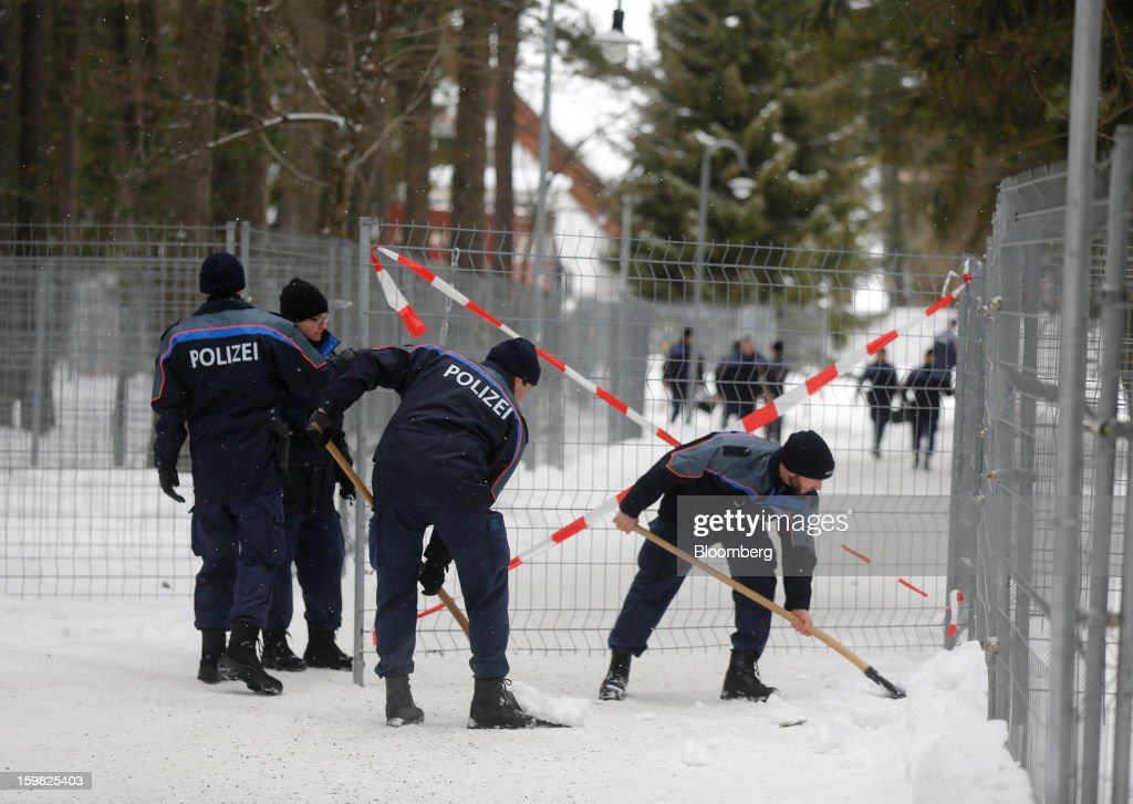 Members of the Swiss police force are seen moving snow from outside the Congress Centre ahead of the World Economic Forum (WEF) meeting in Davos, Switzerland, on Monday, Jan. 21, 2013. This week the business elite gathers in the Swiss Alps for the 43rd annual meeting of the World Economic Forum in Davos, the five day event runs from Jan. 23-27. Photographer: Simon Dawson/Bloomberg via Getty Images