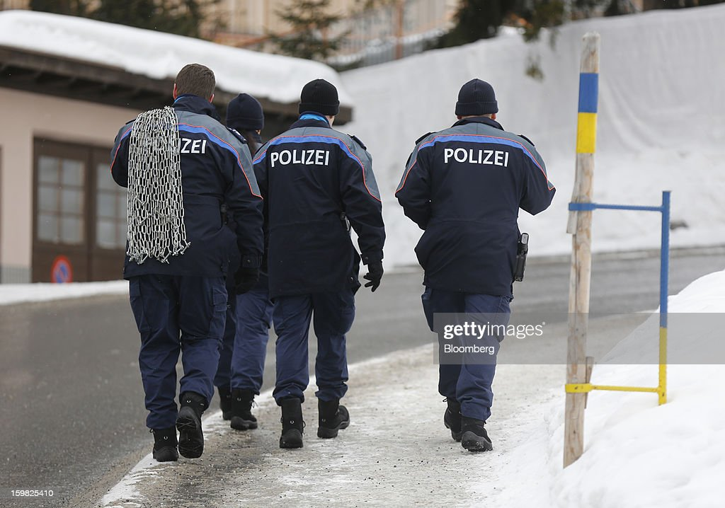 Members of the Swiss police force carry security chains outside the Congress Centre ahead of the World Economic Forum (WEF) meeting in Davos, Switzerland, on Monday, Jan. 21, 2013. This week the business elite gathers in the Swiss Alps for the 43rd annual meeting of the World Economic Forum in Davos, the five day event runs from Jan. 23-27. Photographer: Simon Dawson/Bloomberg via Getty Images