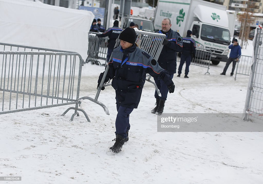 Members of the Swiss police force move a security barrier into position outside the Congress Centre ahead of the World Economic Forum (WEF) meeting in Davos, Switzerland, on Monday, Jan. 21, 2013. This week the business elite gathers in the Swiss Alps for the 43rd annual meeting of the World Economic Forum in Davos, the five day event runs from Jan. 23-27. Photographer: Simon Dawson/Bloomberg via Getty Images