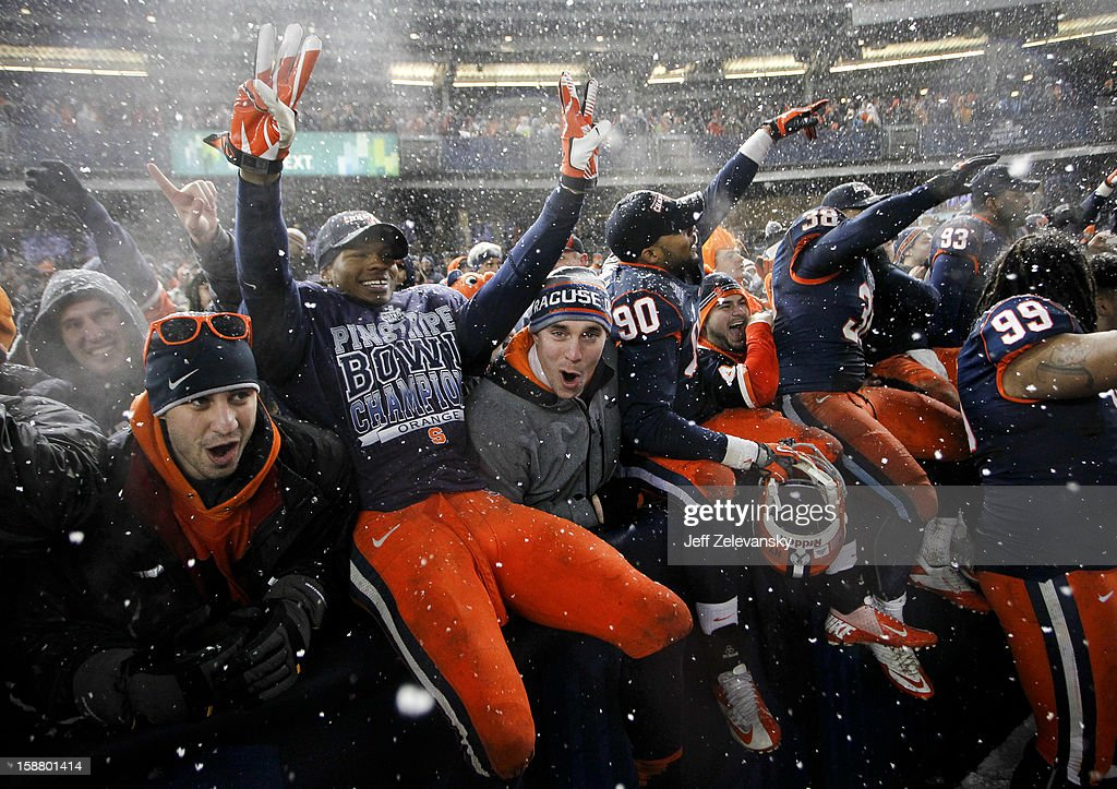 Members of the Syracuse Orange celebrate with fans after their win over the West Virginia Mountaineers in the New Era Pinstripe Bowl at Yankee Stadium on December 29, 2012 in the Bronx borough of New York City.
