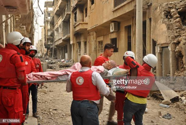 Members of the Syrian Arab Red Crescent carry 90yearold Abu Mahmud on a stretcher out into a destroyed street in the AlSheikh Yassin neighbourhood of...