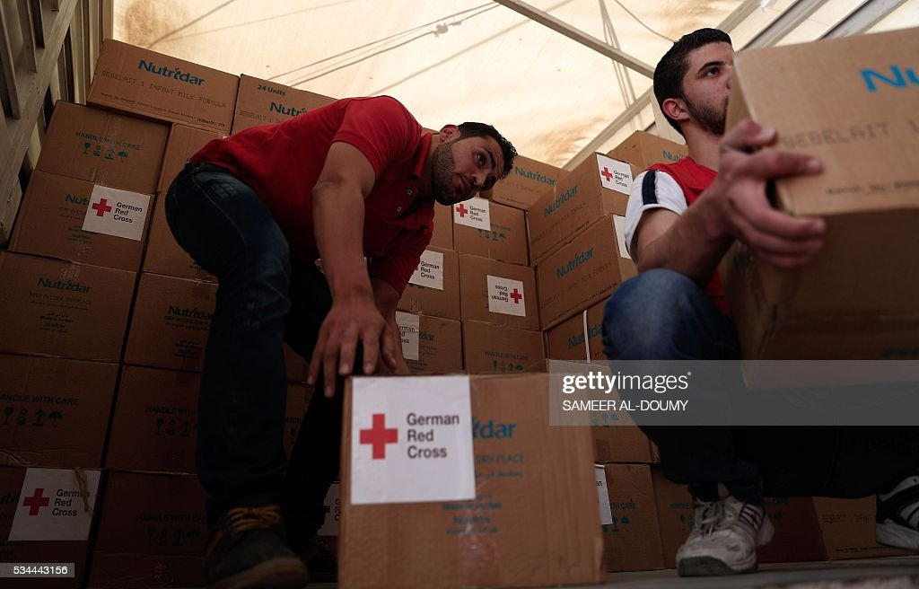 Members of the Syrian Arab Red Crescent deliver aid boxes, some from the German Red Cross, to the besieged rebel bastion of Douma, a flashpoint near the Syrian capital on May 26, 2016. / AFP / Sameer Al-Doumy
