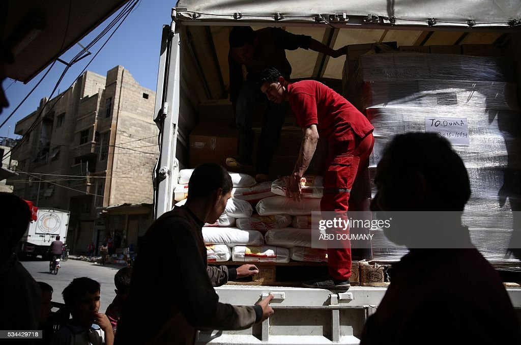 Members of the Syrian Arab Red Crescent deliver aid to the besieged rebel bastion of Douma, a flashpoint near the Syrian capital on May 26, 2016. / AFP / Abd Doumany