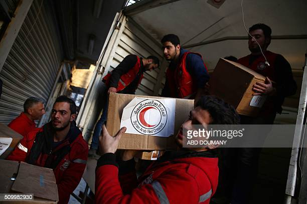 Members of the Syrian Arab Red Crescent unload aid parcels from a lorry on February 13 2016 in the rebelheld city of Douma northeast of the capital...