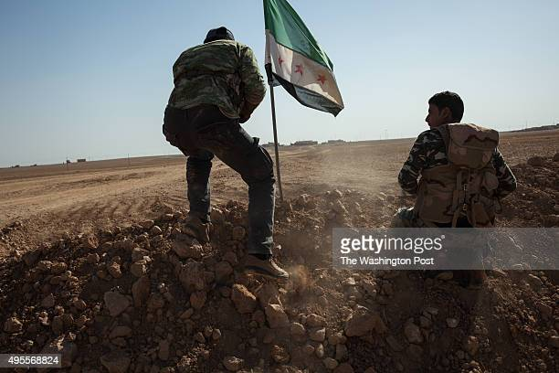 Members of the Syrian armed group Liwa Thuwar alRaqqa hold positions in the frontline against the Islamic State group outside Ayn alIssa in the...
