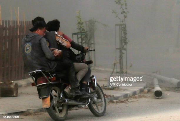 TOPSHOT Members of the Syrian Civil Defence also known as White Helmets evacuate a wounded baby on a motorcycle towards a makeshift clinic in the...