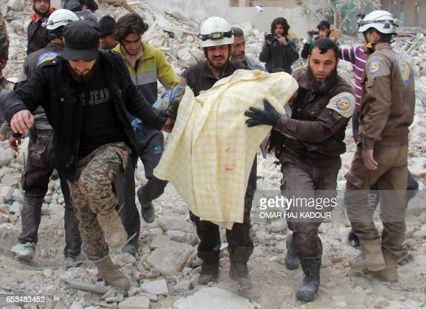TOPSHOT Members of the Syrian civil defence known as the White Helmets remove a victim from the rubble of a destroyed building following a reported...