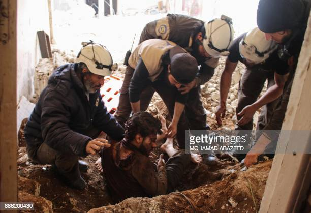 TOPSHOT Members of the Syrian civil defence volunteers also known as the White Helmets remove a victim from the rubble of his house on April 8...
