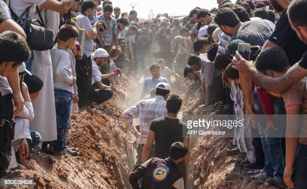 TOPSHOT Members of the Syrian civil defence volunteers also known as the White Helmets bury their fellow comrades during a funeral in Sarmin a...